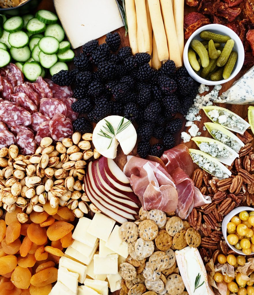 Meat and cheese board. Dried fruits, nuts, meats, pickles, crackers, and vegetables.